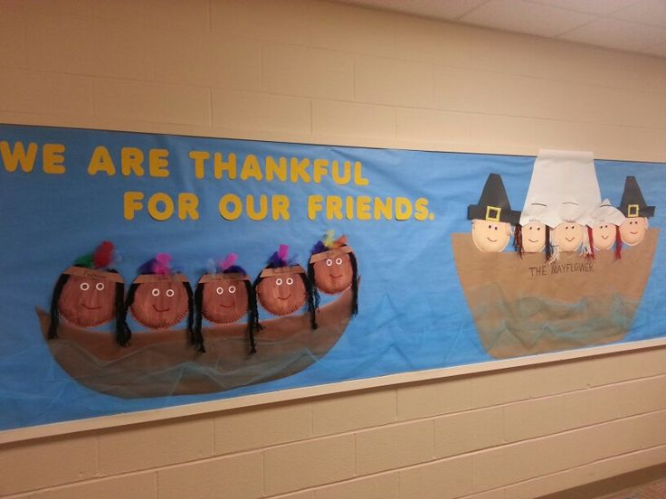"""Thanksgiving bulletin board with Pilgrims in the """"Mayflower"""" and a canoe of Native Americans."""