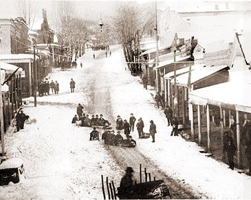 Photo of snowy Grass Valley and residents tobogganing down the Main Street hill. Grass Valley was originally named Centreville when a post office was established in 1851, but renamed Grass Valley the following year. The town incorporated in 1860.  circa 1874