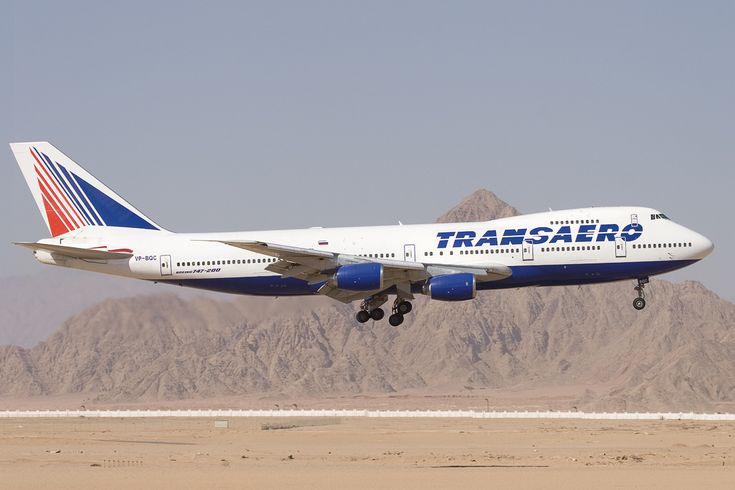 Side view of quadjet landing against a mountain backdrop.