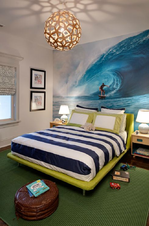 Fun Boy's bedroom with surfer theme. Boy's bedroom with David Trubridge Coral Pendant in Natural. Fantastic wall mural of waves and surfer. Lime green upholstered bed with navy and white striped sheets. Dark green woven rug, simple nightstands and white ceramic lamps.