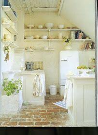 white kitchen with brick floor