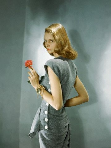 1947 by Horst P Horst Model is wearing a sleeveless, side buttoned, heather gray shirt with matching skirt and bracelets.
