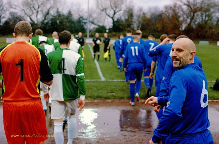Just like old times, Billingham Synthonia v Newton Aycliffe,England year2013 by Stuart Roy Clarke – Two amateur football sides Billingham Synthonia and Newton Aycliffe walk out amidst puddles for team line-ups alongside match officials. The one player at the back in turning to acknowledge someone saying something to him shows …