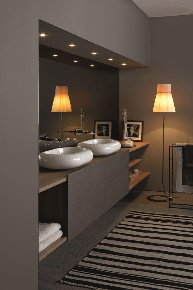Móvel para lavatório Monterosso Agua, com plano de apoio e prateleiras Rovere Cherry e portas com acabamento Tex Ferro, além de parede revestida de espelho fumê
