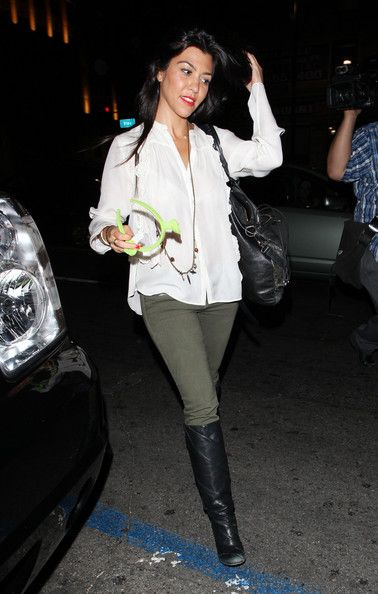 Kourtney Kardashian in a pair of olive skinny jeans and knee-high boots, completed with a white blouse.