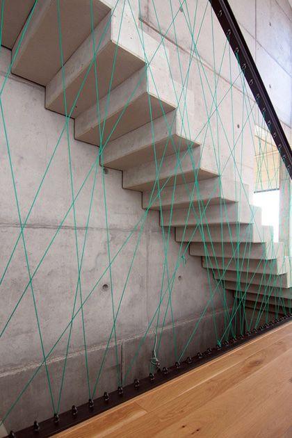 Boa ideia: Para suavizar o visual pesado da escada de concreto, a equipe do escritório MO Architekten bolou um guarda-corpo delicado e original, que quebra a rigidez do acabamento. Fixados no piso …
