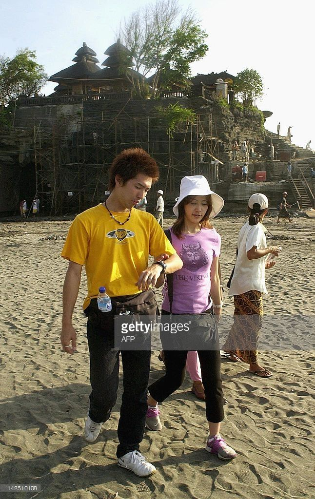 A Japanese couple walk along the beach near the complex of the Tanah Lot temple on the western coast of Bali, some 30 km from Denpasar, 23 October 2002. Despite a drop in tourist visits to the area of Kuta, near Denpasar, following the 12 October bombing that killed more than 190 people, many visitors can still be found at other areas of the island. AFP PHOTO/Oka BUDHI