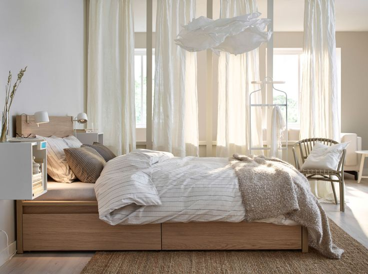A bed in oak with bed textiles in white, beige and light brown.