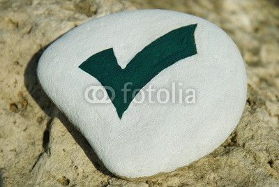 haken check mark symbol on a stone over the rock