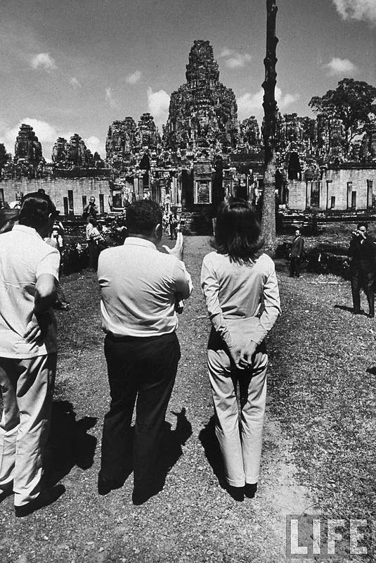 """vintage everyday: November 1967 – With a radiance now as famous in Phnom Penh, Cambodia as it is in Paris, Jacqueline Kennedy, America's unofficial roving ambassador, visited that ancient Asian land to fulfill """"a lifelong dream of seeing Angkor Wat,"""" stone ruins from the romantic Khmer civilization in the 12th Century. Here with David Ormsby-Gore visiting the Temple of Bayon, near Angkor Wat."""