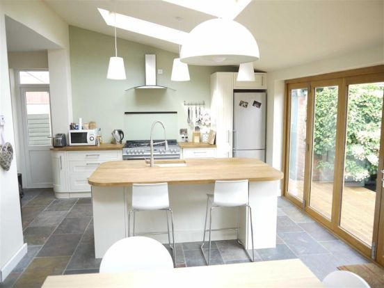 Velux pine finish centre pivot roof windows match the wooden trim of this kitchen extension.