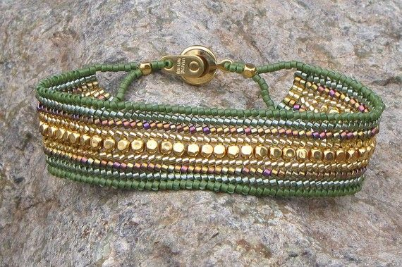 """Ribbons of olive green and gold are featured in this herringbone stitch bracelet. The gold metal beads down the center give it the ability to be worn for casual or work.  The button style clasp is gold-plated. The bracelet measures 7 1/4"""" in length and close to 3/4 inch wide. This bead-woven bracelet has been well reinforced and has a wonderful smooth texture that is very comfortable to wear."""