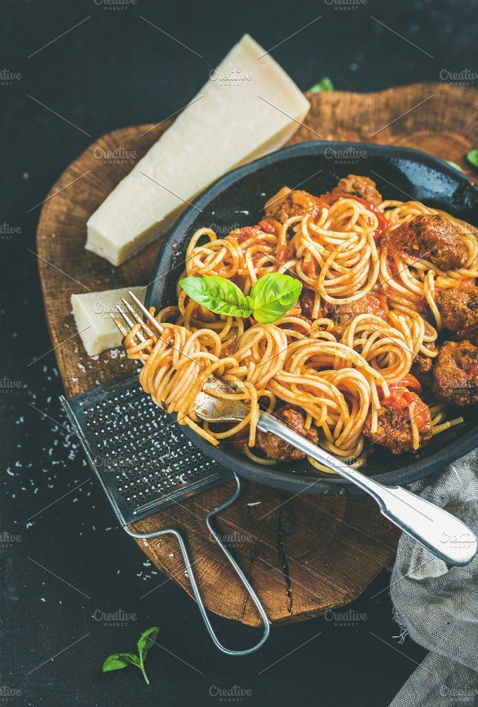 #Italian dinner with meatballs  Italian pasta dinner. Spaghetti with meatballs basil and parmesan cheese in black plate over dark rustic wood background selective focus Slow food concept