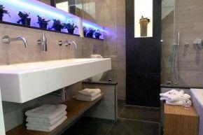 Extra brede wastafel in badkamer met inloopdouche. Deze badkamer bestaat eigenlijk uit twee delen. Het voorste deel bestaat uit een extra brede wastafel en het ligbad. Het achterste, en tevens kleinste deel, omvat de urinoir en de inloopdouche. De twee delen worden gescheiden door twee glazen wanden. MD Design
