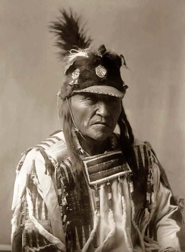 Here for your enjoyment is an exciting photograph of Forked Iron, a Crow Brave. It was made in 1908 by Edward S. Curtis.    The photo illustrates a Head-and-shoulders portrait of this fine looking Crow Brave.