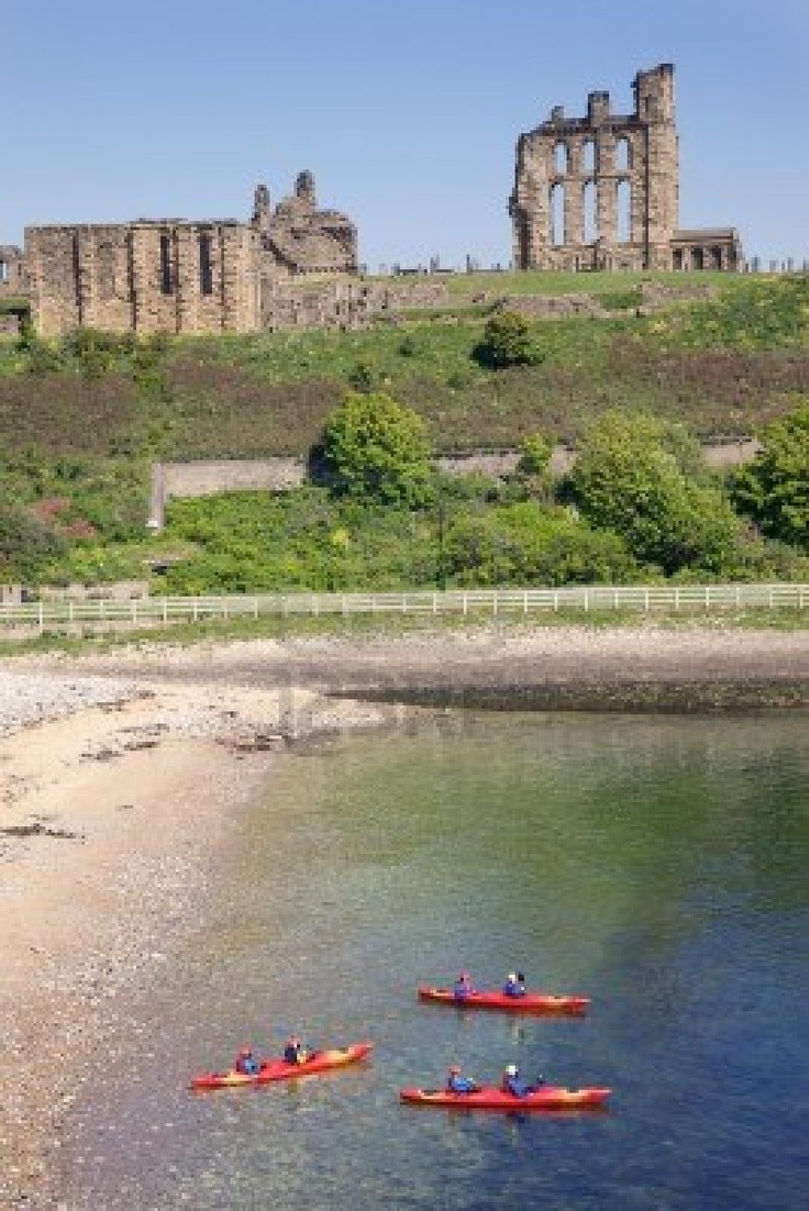 Tynemouth, UK, Kayakers in front of Tynemouth Castle and Priory on the coast of North East England . The ancient buildings overlook the North Sea and the River Tyne.