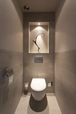 Nook above toilet with statue and lighting - awesome!