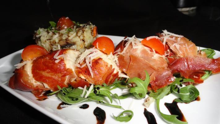 Pollo Involtini: Delicioase rulouri de tradiție străveche italiană, preparate din file de piept de pui, cu roșii uscate și mozzarella și învelite cu feliuțe de prosciutto crudo, totul rumenit la cuptor.
