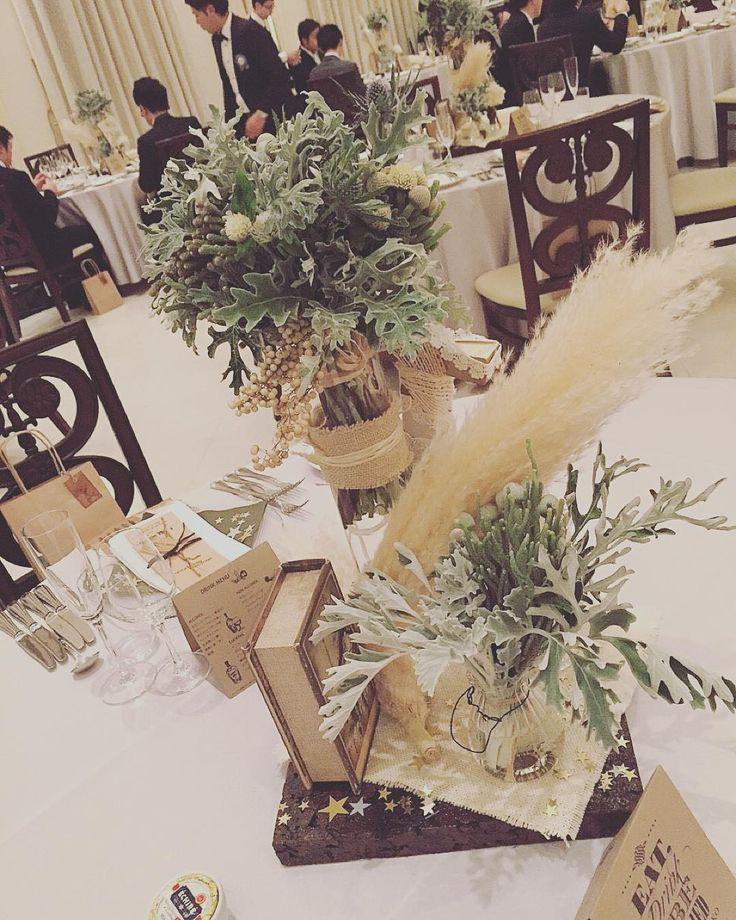 「. wedding report 2 ゲストテーブル装花 . ダスティミラー、パンパスグラス、ペッパーベリー 素敵な花材でいっぱい。 見事にお花系は無しでした。 高さを出して、洋書も合わせて、 とってもシックなコーディネート! 打ち合わせの時に彼がこんな感じのコーディネートがいいって提案くれました(⊃´▿`…」