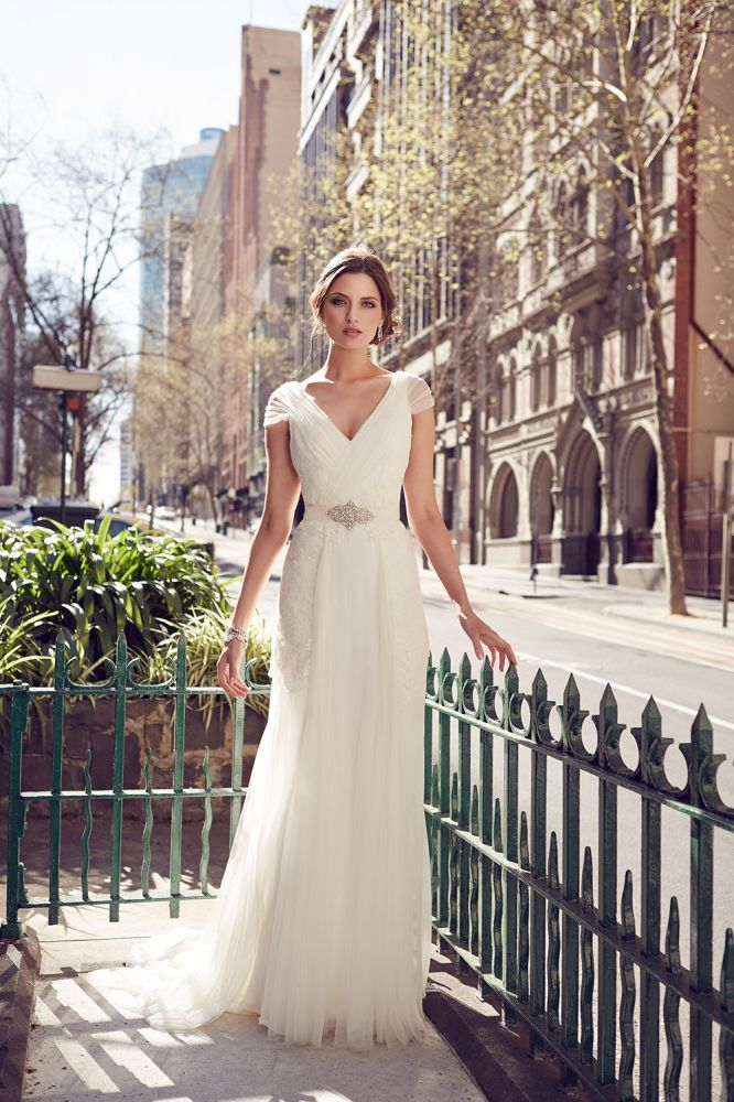 Elegant v-neck cap sleeve slim wedding dress with lace bodice. Center front and back tulle draped across the bodice and into a softly fluted cap sleeves skirt. Matching with sash.