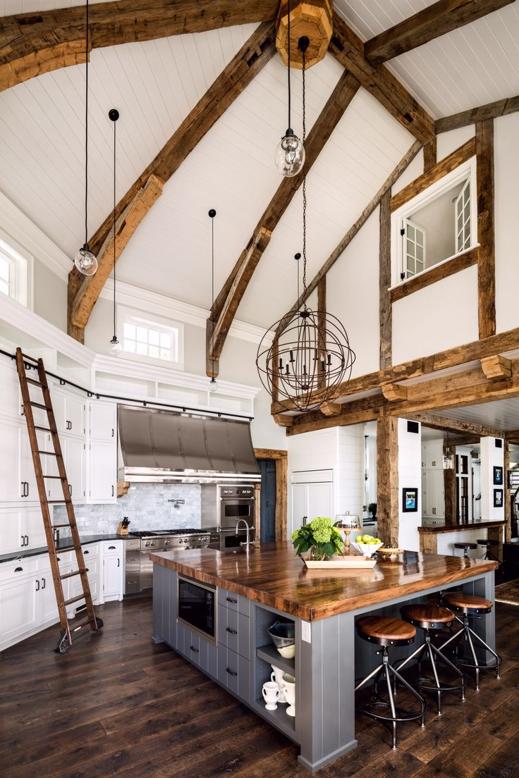 Stunning country kitchen features a double-height vaulted ceiling with exposed joists and a loft window overlooking the space in this home designed by Wade Weissmann Architecture. [1200 × 1800]