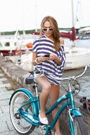 Girl with bicycle standing on the sea and yacht background Outdoors lifestyle Stock Photo