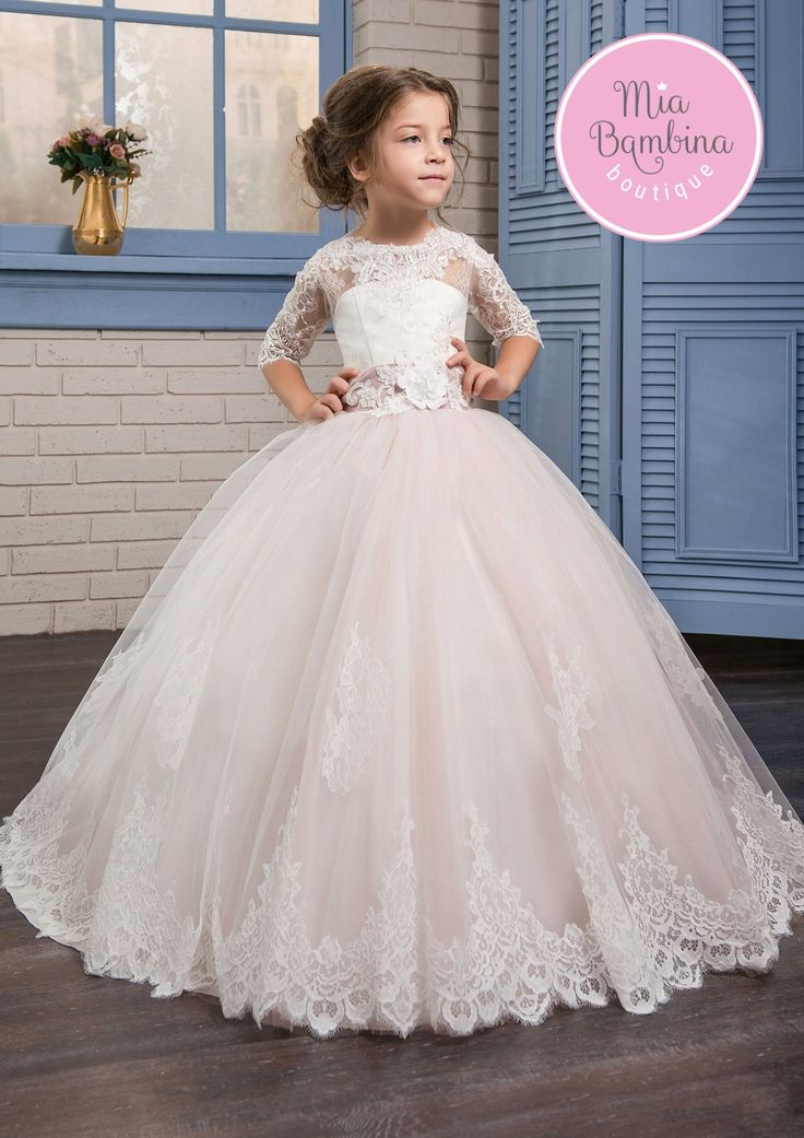 The Salinas is a flower girl dress with beautiful white lace overlaying a sweetheart bodice with half-length lace sleeves and a multi-layered tulle skirt. The floral lace motif completes the skirt hem
