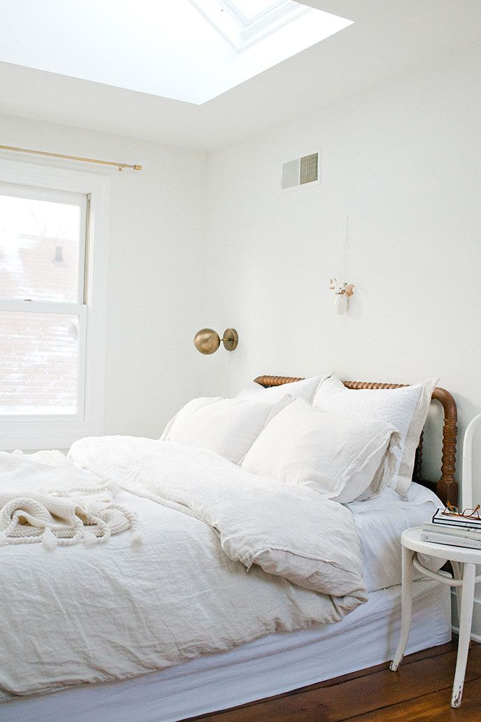 This white bedroom features a gold sconce and a beautiful wooden bed frame