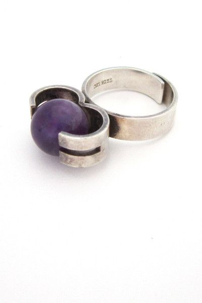 "Elis Kauppi for Kupittaan Kulta rolling ring, sterling silver, amethyst size: setting 3/4"" x 1/4"", sphere 7/16"", ring size 6 1/2 adjustable Elis Kauppi was at the forefront of modern jewellery design in Finland beginning in the fifties, winning numerous awards with his sleek and minimalist designs. This ring features an amethyst sphere set to allow it free movement within its bold mount: the stone can be rolled to display either clear, dark purple or the streak of white running through it."