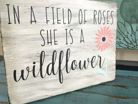 "This listing is for a hand painted sign that reads: ""In a Field of Roses She is a Wildflower"". The sign is completely handmade from wood that has been sanded, stained and hand painted. This would make a wonderful addition to any home decor. The sign is finished in a whitewashed/distressed look with black lettering. The flower can be any color you would like, just be sure to select whatever color will best match your decor. If choosing custom, please make sure to tell me exactly what you"