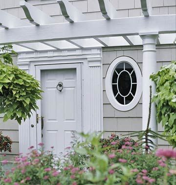 An oval window (one of a pair flanking the door) adds architectural interest to the facade of this house. It admits light without sacrificing privacy.