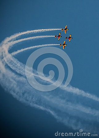 A team of four airplanes in red blue and yellow flying together high up in the sky on an air show.  Airplanes on air show with smoke trails. Airplane performing difficult maneuver in the sky. Blue clear sky. Blue background.