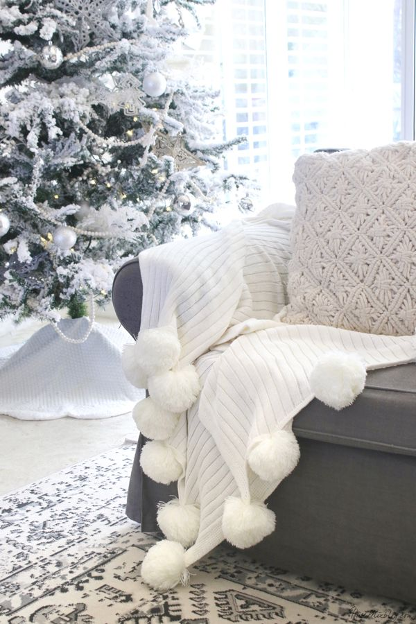 All white Christmas decor - flocked tree and pom pom blanket