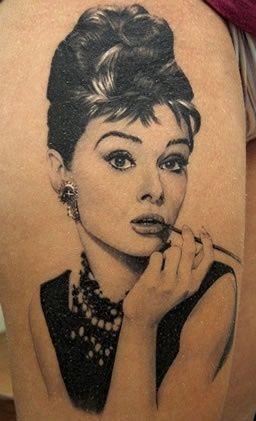 Bandanna in hair, Jack Daniels shirt, L's, gauges, tattoos on arm of skeleton Marilyn etc.