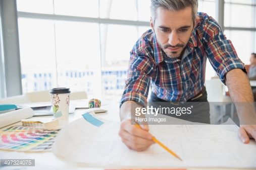 Stock Photo : Creative businessman looking at blueprint in office