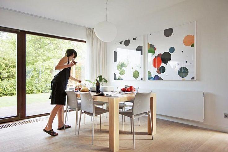 Na míru vyrobený masivní dubový stůl doplňují subtilní designové židle v oblíbené šedé. Stěny zdobí obrazy, nad jídelním stolem geometrické ...
