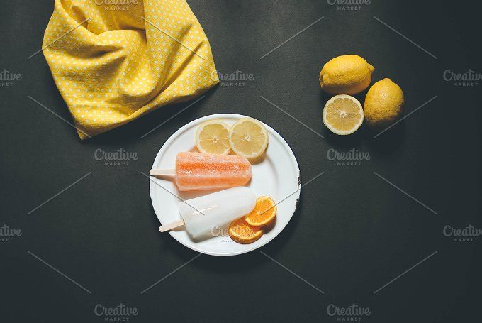 Citrus popsicles on a plate. by Gnesa on @creativemarket