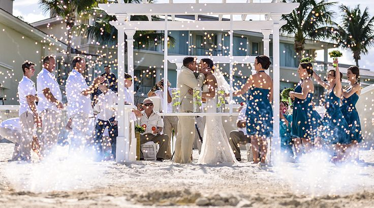 Perfect shot of the first kiss as husband and wife at this beach wedding. The picture frame! The fireworks! | Palace Resorts Weddings ® #destinationwedding