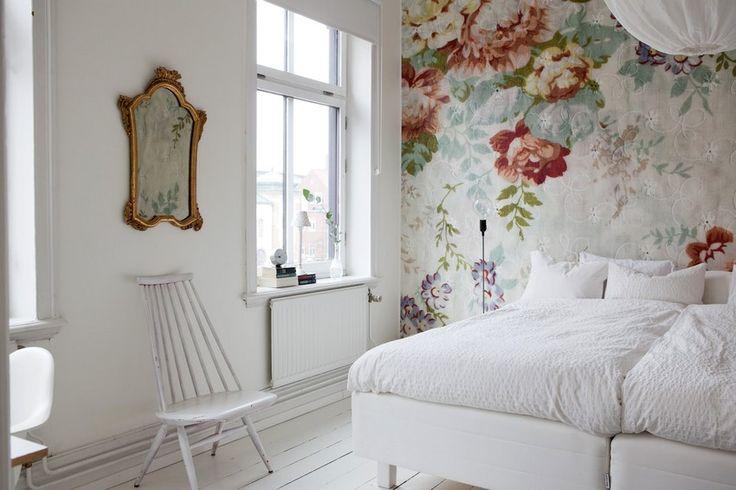 Обоями с рисунком оклеена стена позади кровати