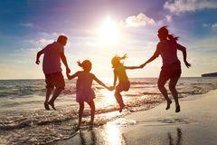 Familia feliz que salta en la playa Foto de archivo libre de regalías