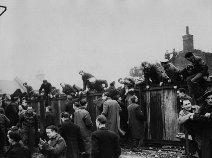 ootball fans climbing over a fence at Upton Park football ground to watch the cup tie between West Ham and Arsenal, London, 5th January 1946. (Photo by Central Press/Picture Post/Hulton Archive/Getty Images)
