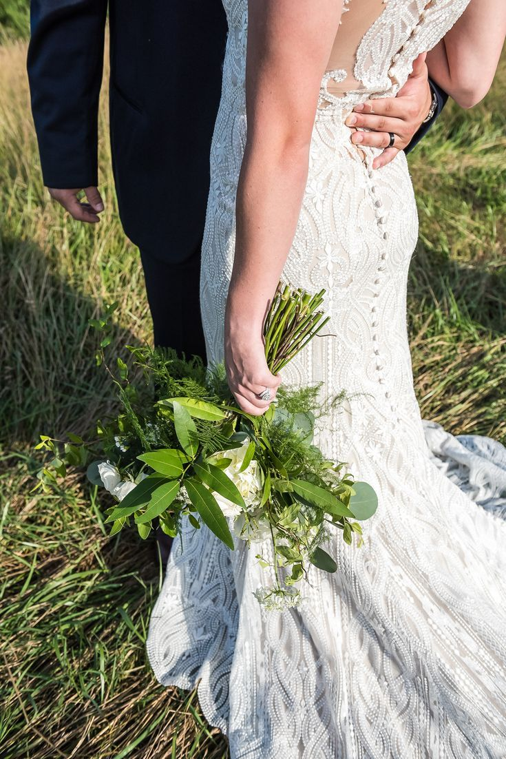 Beautiful Lace Back Wedding Dress And Bride Holding A Green