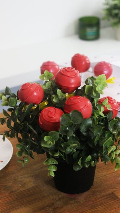 Recipe with video instructions: Why have fresh flowers when you can get rose-shaped red velvet cake pops instead? Ingredients: 375 grams red velvet cake, 100 grams white chocolate chips, melted, 65 grams whipping cream, hot, 300 grams red candy melts, melted, Lollipop sticks, Yellow ribbon, Red luster dust