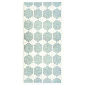 Anna Plastikteppich von Brita Sweden wird von einem aquafarbigen, grafischen Muster auf weißem Hintergrund geprägt. Dieser stilreine, multifunktionelle Teppich ist sogar in der Waschmaschine waschbar, und hat dadurch ein viel breiteres Einsatzgebiet als herkömmliche Teppiche: in Nassräumen, in der Küche, im Eingangsbereich, auf Balkon und Terrasse. Da Anna nach dem Jacquard-Verfahren gewebt wird, zeigt sich beim Wenden dasselbe Muster in gegensätzlicher Farbkonstellation.