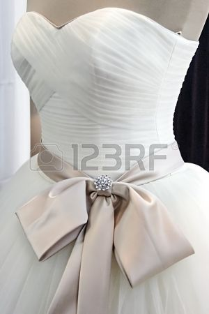 Detail of a wedding dress decorated with crystals, veils, ribbons and knot