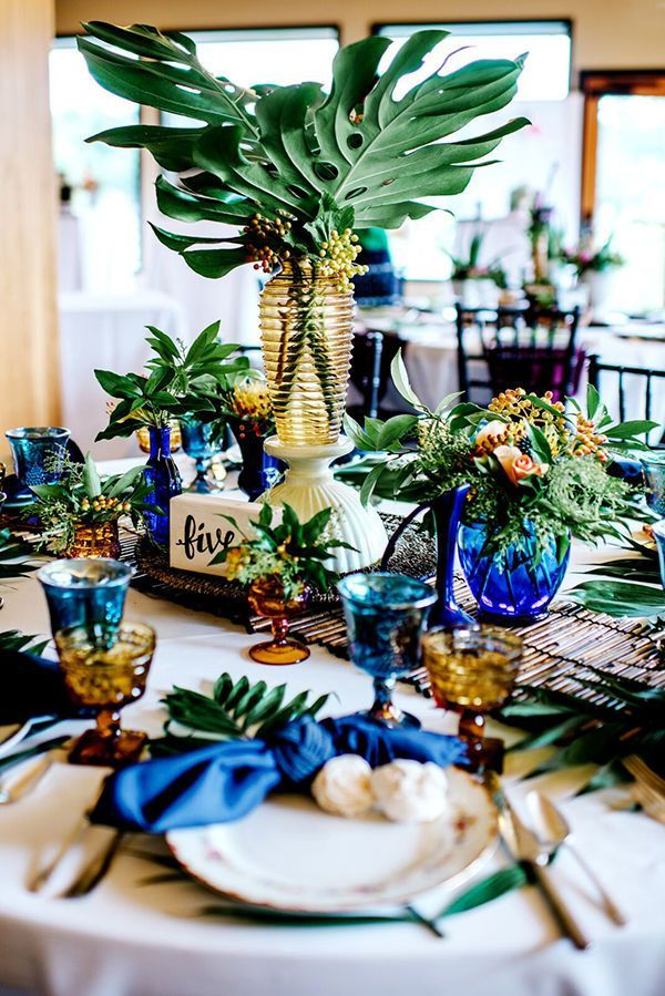 Tropical Wedding Table Decorations: A creative centerpiece mimicks a palm tree, with a yellow glass vase and palm leaves. A bamboo table runner, blue and yellow glassware and a calligraphy table number are just some of the sweet details that stand out at this reception table!