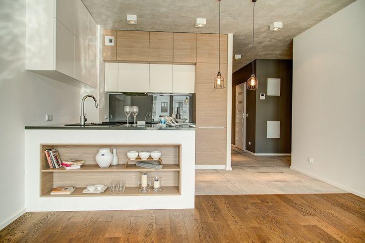 Kuchnia otwarta na salon. Szafki kuchenne zabudowane pod sam sufit. Fronty szafek w 2 kolorach: białym macie i jasnym drewnie nadają wnętrzu minimalistyczny charakter.