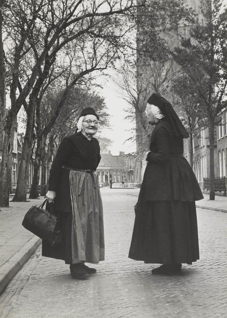 Twee vrouwen in Terschellinger streekdracht. Ze dragen een schootjak, een rok en een schort. Op het hoofd dragen ze een muts, met daarover de 'zwarte kap'. Om de hals een kralensnoer met slot. 1950-1975 #Terschelling