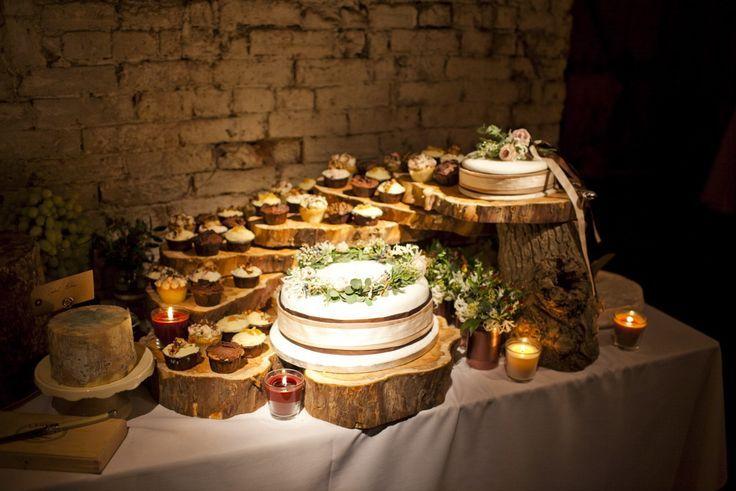 déco mariage champêtre - candy bar thématique avec un gâteau blanc et des cupcakes sur des présentoirs en bois
