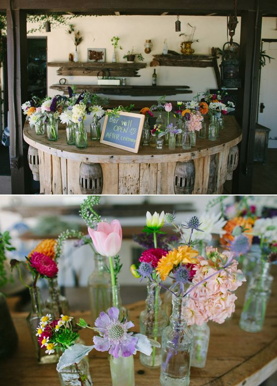 rustic bottle vases filled with colorful flowers